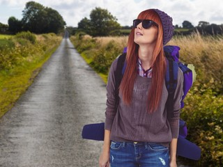 Composite image of portrait of a hipster woman with a travel bag