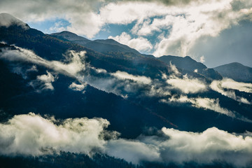 Amazing view of Slovenian mountains near Bled, Slovenia. Sunshine behind foggy mountains after a rainy day.