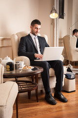 Young businessman working with portapble computer sit on armchair.