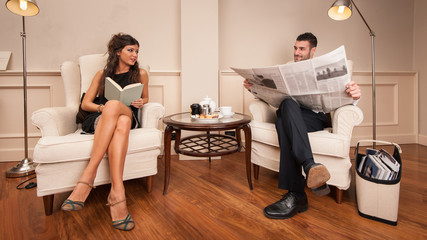 Young couple relaxing while reading sit on armchairs in luxury h