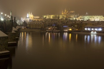 Night romantic snowy Prague gothic Castle with Charles Bridge, Czech republic