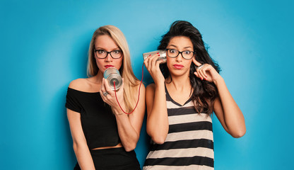 Young women talking with tin can telephone against blue background.