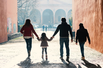 Happy family walking together in the city.