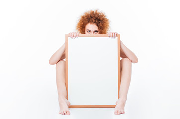 Naked woman sitting on the floor with blank board