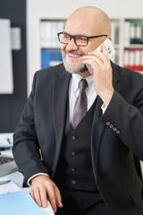 zufriedener geschäftsführer am telefon