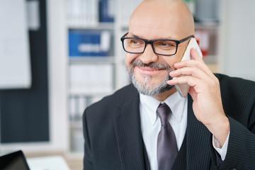 geschäftsmann mit anzug telefoniert im büro