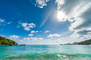 Indian Ocean Water and beach in Seychelles, Mahe island. Mountain and forest in Background