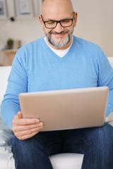mann sitzt zuhause auf dem sofa und surft im internet