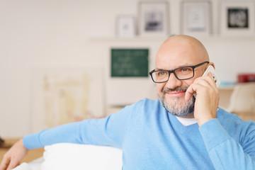 entspannter mann telefoniert zuhause mit seinem handy