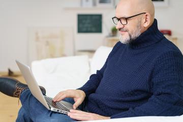 älterer mann mit brille surft im internet