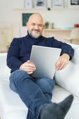 mann liegt auf dem sofa und schaut auf tablet-pc