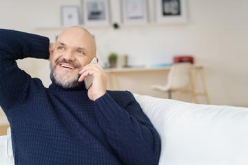 mann sitzt auf dem sofa und telefoniert