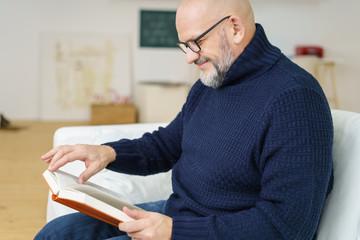 älterer mann mit brille liest ein buch