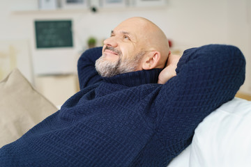 älterer mann lehnt sich entspannt zurück