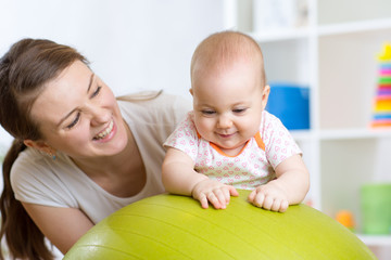 Mother with child doing exercises with green gymnastic ball at home. Concept of caring for the baby's health.