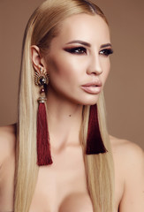 fashion photo of beautiful sexy woman with blond hair and extravagant makeup, posing in studio