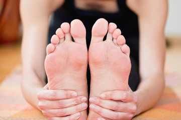 Yoga feet. Detail from Paschimottanasana or seated forward bend yoga pose