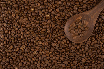 Wooden spoon on roasted coffee beans, background.