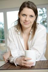 Frau trinkt zu Frühstück oder Brunch eine Tasse Kaffee und macht Pause