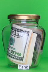 Money in glass jars, on Green background with sign - Bank
