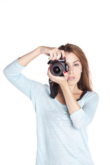 Woman taking a photograph with a reflex camera.  Isolated on white background