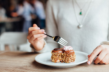 Woman eating cake in cafe