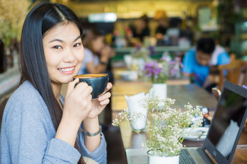 Beautiful asian woman using laptop inside coffee shop