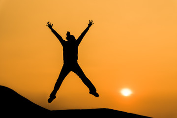 Silhouette of woman in happy jump on orange sunset sky