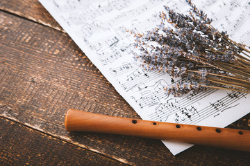 Flute with notes and lavender on the wooden table
