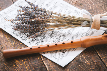 Flute with notes and lavender on the wooden table horizontal