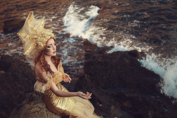 Beautiful fashionable mermaid sitting on a rock by the sea