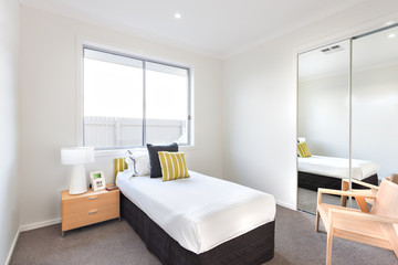 Modern bedroom with a single bed and white sheets near a mirror