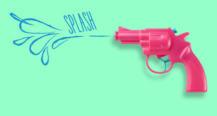 Pink water-gun on green background