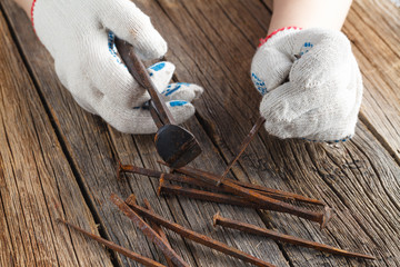 pliers and few rust nails on wood background