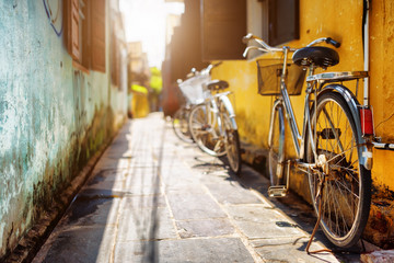 Bicycles parked near yellow wall of old house on sunny street