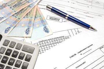 Calculator, pen, money and primary documents for payroll