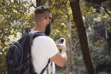 Man hiker taking photo with smart phone at autumn forest
