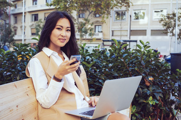 Portrait of a beautiful young asian well-dressed business woman holding on her portable laptop computer while sitting on a wooden bench and chatting on the smart-phone