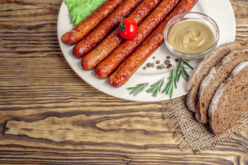 grilled sausages with tomato and rosmarine on plate at wooden