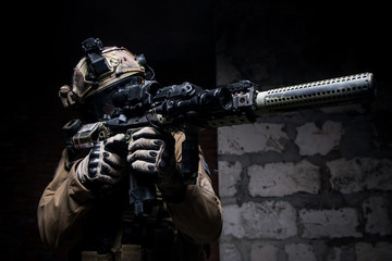 Soldier in military ammunition with gun/Man in military uniform and ammunition aiming from rifle on background of brick wall