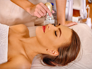 Close up of lying young woman with closed eyes receiving electroporation  facial therapy at beauty salon.