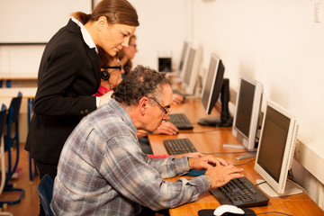 Group of adults learning computer skills. Intergenerational tran