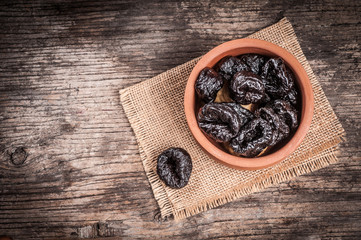 Dried plums in clay bowl