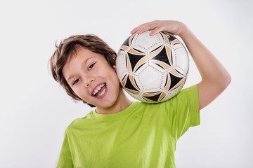 Cute Smiling Kid Holding Soccer Ball on the Shoulder