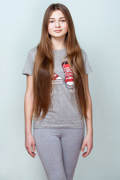 Portrait of a beautiful smiling teenage girl with long hair in gray T- shirt and pants