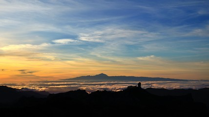 Vibrant sunset with Roque Nublo in foreground and Tenerife island in background, Canary islands