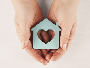 Female hands with model of house on wooden table background