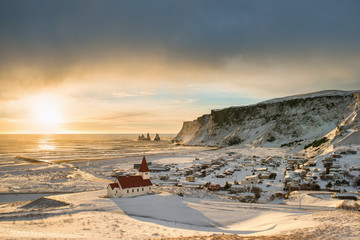 Beautiful view of the small town Vik near Reynisfjara coast and the mountains in winter Iceland in the sunny day