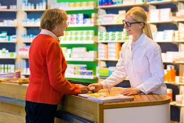 Customer receiving medication from pharmacist.