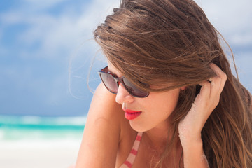 woman with red lips, long hair and in sunglasses